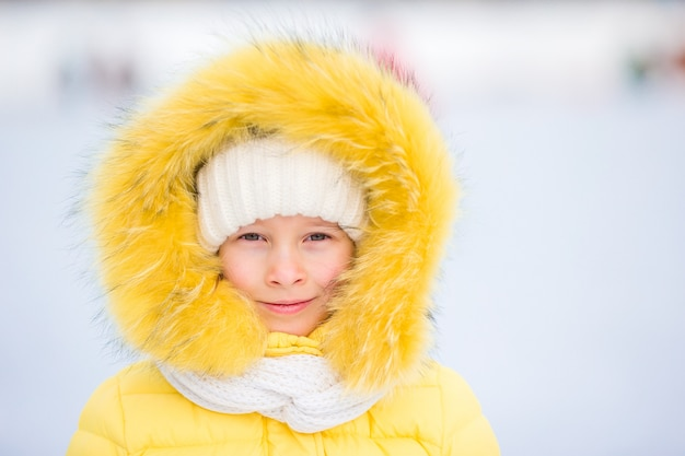 Portrait of little adorable girl with beautiful green eyes in snow sunny winter day