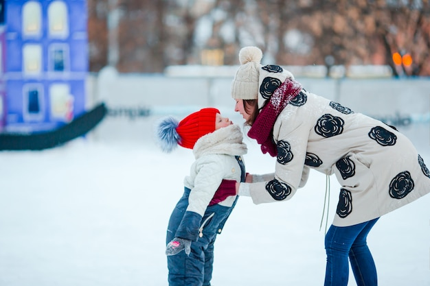 Portrait of little adorable girl and young mother skating