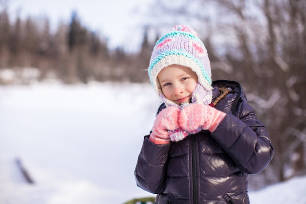 Portrait of little adorable happy girl in the snow sunny winter day