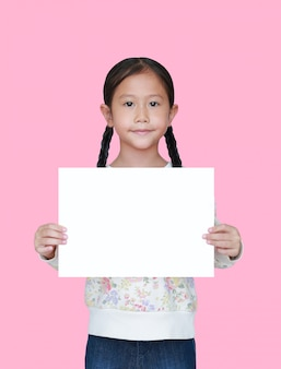 Portrait little asian child girl showing blank white paper isolated on pink background. kid holding empty white square copy space