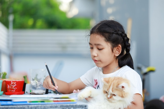Portrait of a little asian girl doing homework and hugging her persian cat with happiness, select focus shallow depth of field