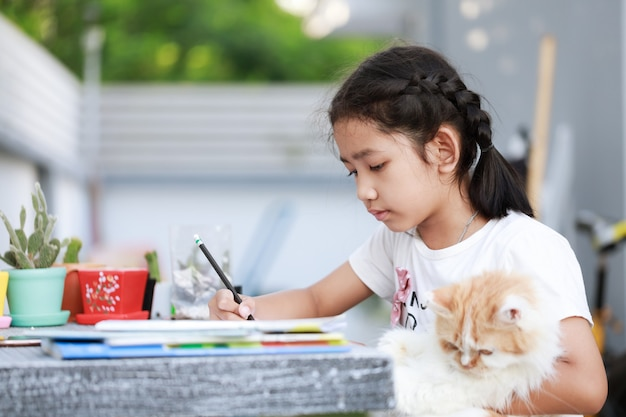 Portrait of a little asian girl doing homework and hugging her persian cat