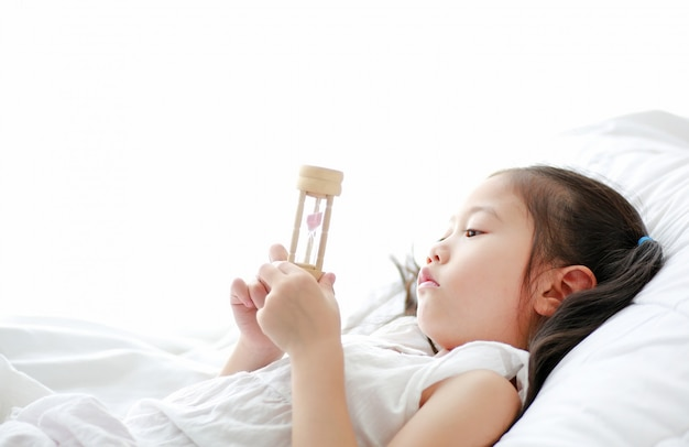 Portrait of little asian girl looking at hourglass in hand lying on bed at home