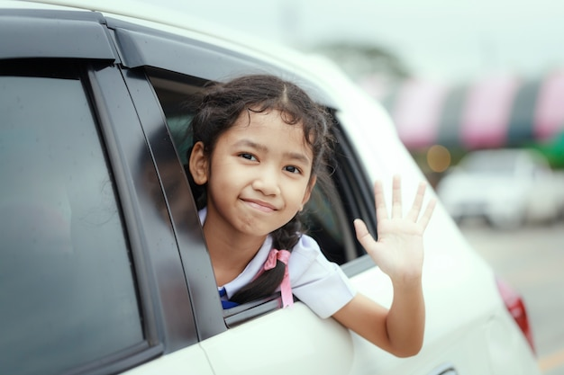 Portrait little asian girl in thai student kindergarten uniform smiling with happiness in the car select focus shallow depth of field