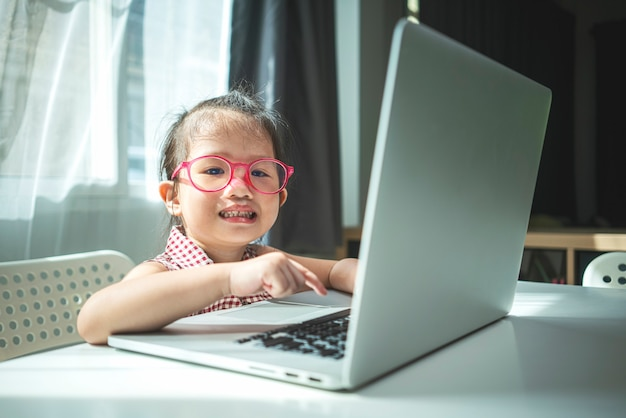 Portrait of little asian girl using laptop computer for online application studying at home. homeschooling, online learning or education concept