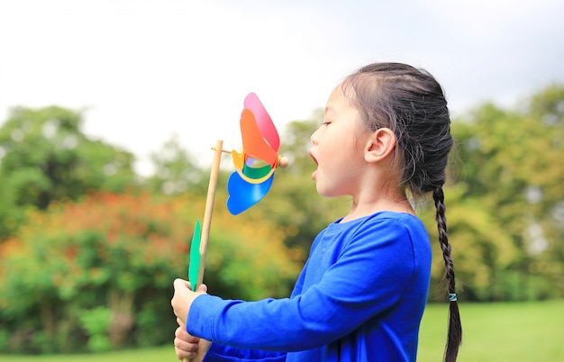 Portrait of little asian kid girl blowing wind turbine in the summer garden.