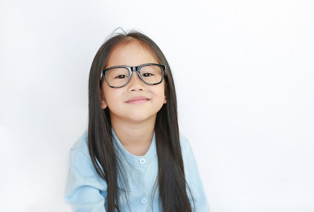 Portrait of little asian kid girl wearing glasses against white background.