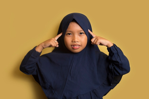 Portrait of a little asian muslim hijab girl  thinks