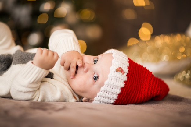 Portrait of little baby boy in red santa's cap laying on a bed against christmas lights.