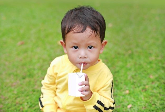 Portrait of little baby boy in sport cloth drinking milk from box with straw in the garden.