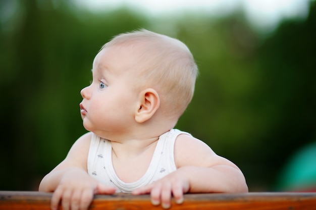 Portrait of little baby boy standing on wooden bench