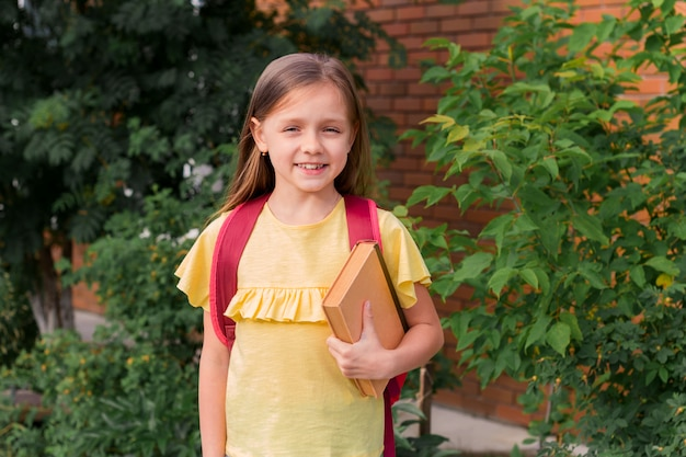 Portrait of a little beautiful girl with a backpack holding book and smiling on a brick wall and green bushes