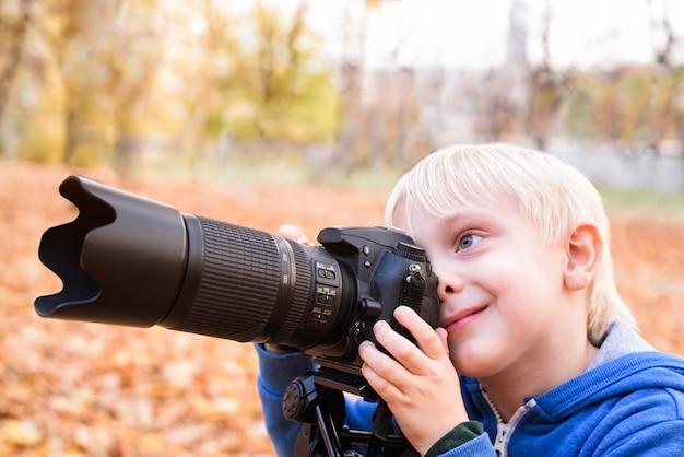 Portrait of little blond boy taking pictures