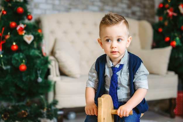 Portrait of little blonde boy sitting on wooden rocking horse in decorated studio. room with sofa and christmas trees with red christmas decorations. cozy atmosphere.