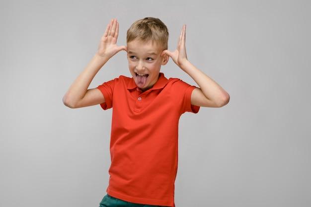 Portrait of little blonde caucasian happy smiling boy in orange t-shirt on gray background