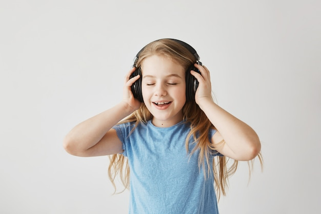 Portrait of little blonde girl in blue shirt playing with big wireless headphones, listening to music, singing song and dancing with closed eyes while nobody home.