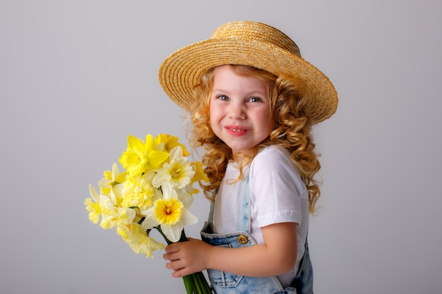 Portrait of a little blonde girl holding a bouquet of spring flowers in a straw hat on a white space