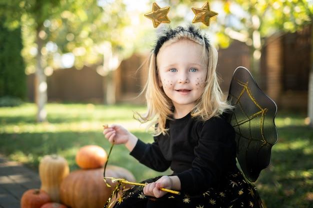 Портрет маленькой блондинки в карнавальном костюме ведьмы на хэллоуин на природе