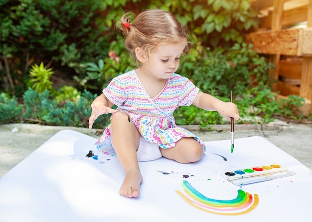 Portrait of little blonde girl painting, summer outdoor.