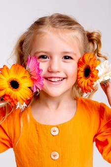 Portrait of a little blonde girl with a bouquet of spring flowers on a light wall