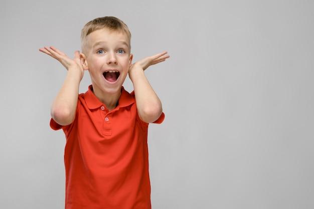 Portrait of little blonde surprised caucasian happy smiling boy in orange t-shirt fooling on gray