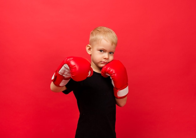 Portrait of a little boy athlete in red boxing gloves making a punch on red