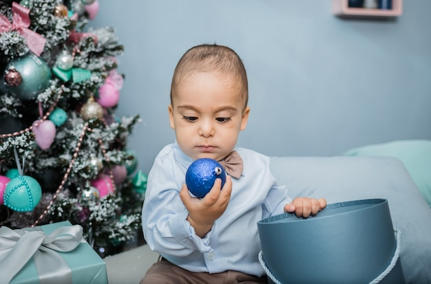 Portrait of a little boy in a blue shirt with a balloon toy sitting on a bed against  a christmas tree
