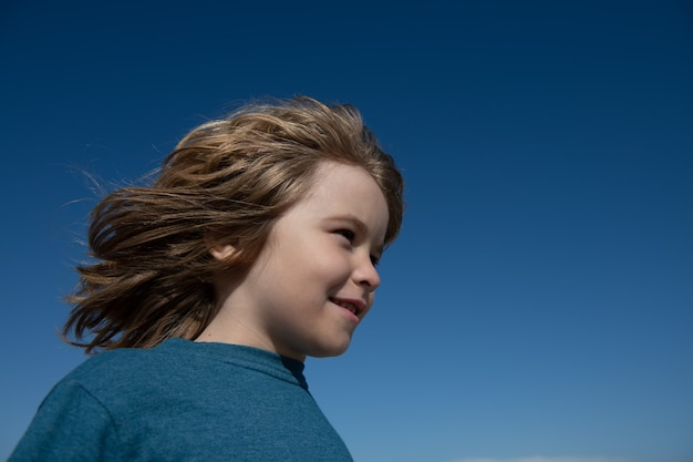Portrait of little boy on blue sky with copy space. concept of kids looking away face close-up. head shoot children portrait.