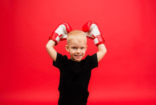 Portrait of a little boy boxing champion in red boxing gloves raised his hands up on a red wall