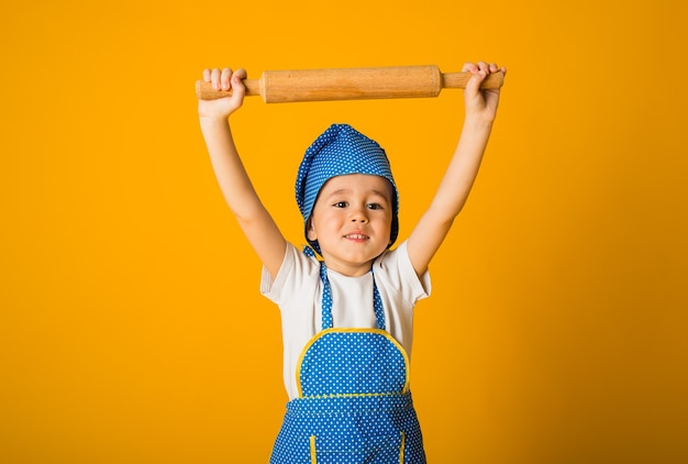 Portrait of a little boy in a chef's hat and apron holding a rolling pin on a yellow surface with space for text
