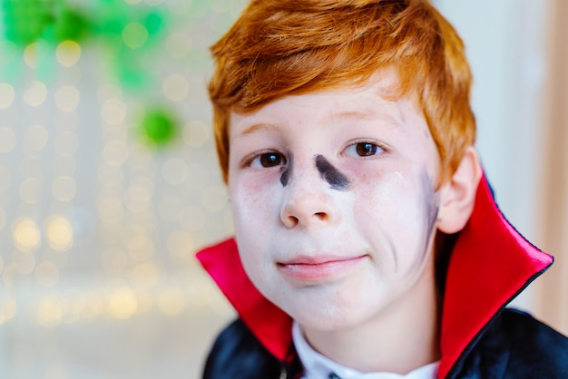 Portrait of little boy dressed as a vampire with makeup for halloween spooky costume party