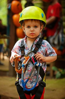 Portrait  little boy having fun in adventure park loking to camera wearing helmet and safety equipment