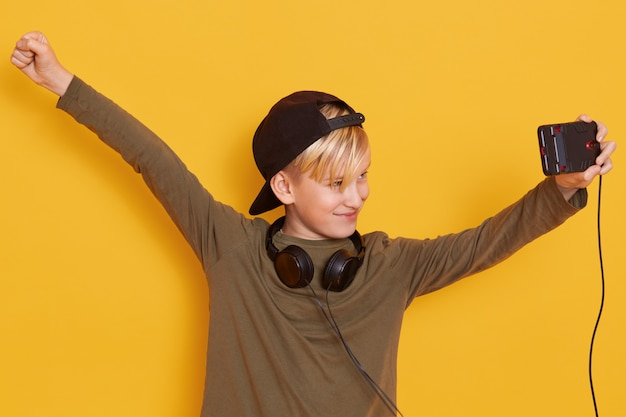 Portrait of little boy holding his modern cellphone and watching video, using wireless internet and headphones, rejoice with hands up