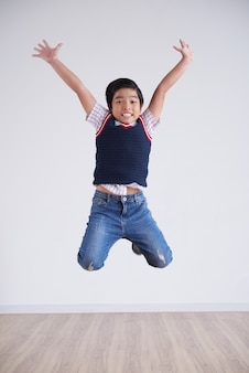 Portrait of little boy jumping happily high in the air