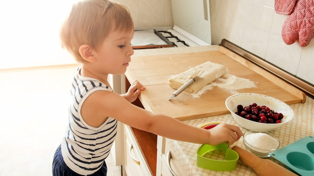 Portrait of little boy making dough on wooden kitchen counterboard. child baking pies or cookies for nreakfast