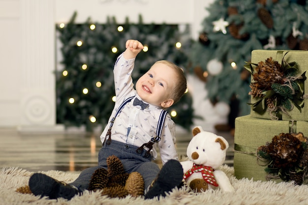 Portrait of a little boy play with pine cones  near a christmas tree. christmas decorations. merry christmas and happy new year .
