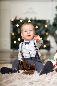 Portrait of a little boy play with pine cones  near a christmas tree. christmas decorations. merry christmas and happy new year