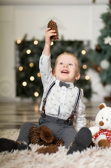 Portrait of a little boy play with pine cones  near a christmas tree