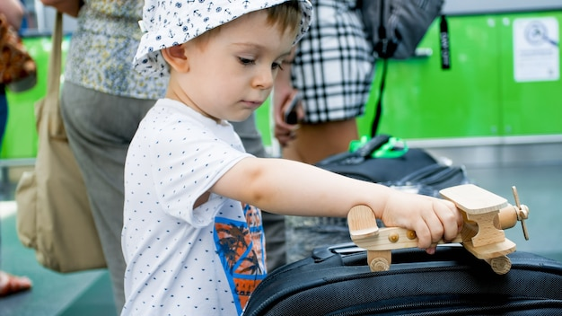 Portrait of little boy playing with wooden toy airplane in modern airport terminal.