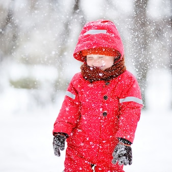 Portrait of little boy in red winter clothes having fun with snow during snowfall