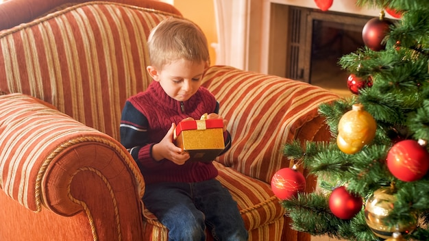 Portrait of little boy sitting in big armchair and holding christmas gift box from santa claus