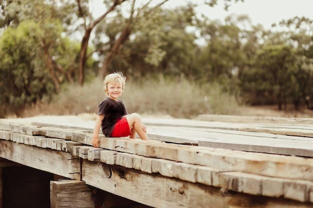 Portrait of a little boy sitting in a pretty garden
