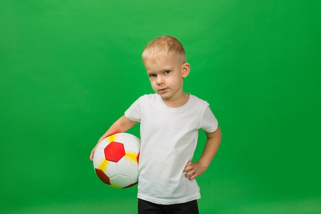Portrait of a little boy soccer player in a white t shirt with a soccer ball on green