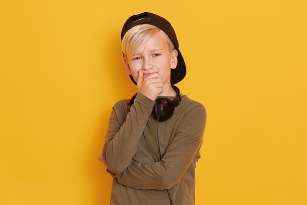 Portrait of little boy wearing black cap, cute guy posing isolated over yellow, male kid covering mouth with hands