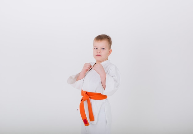 Portrait of a little boy in a white kimono with an orange belt standing in a pose on a white wall