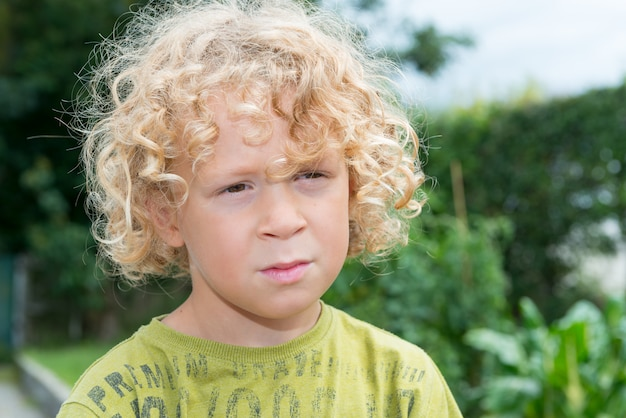 Portrait of  little boy with blond and curly hair