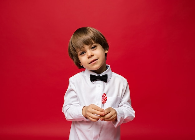 Portrait of a little boy with a lollipop on red