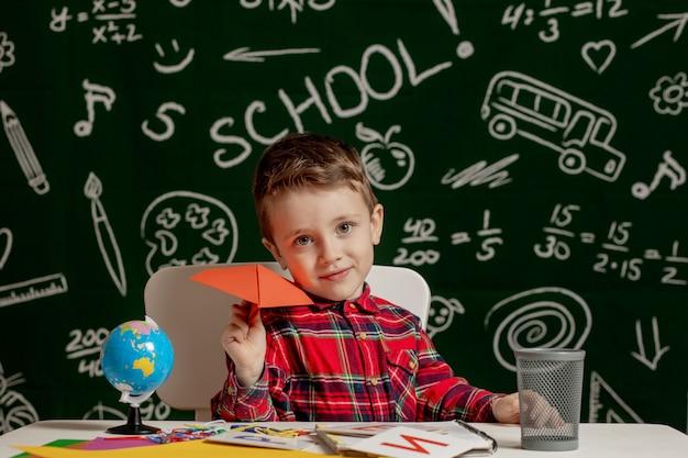 Portrait of a little boy with a paper plane