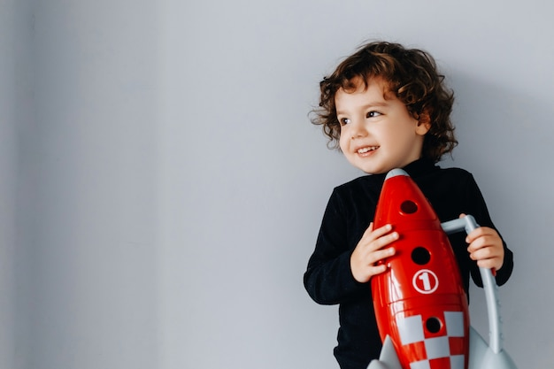 Portrait of a little boy with a red spaceship in his hands on a gray wall