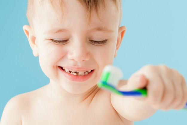 Portrait of little boy with toothbrush on blue.